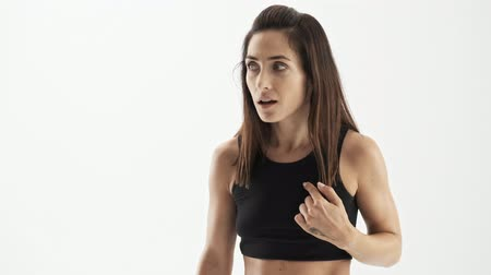 confuso : Shocked attractive sporty brunette woman in black sportswear becoming confused and pointing at herself with finger over white background isolated