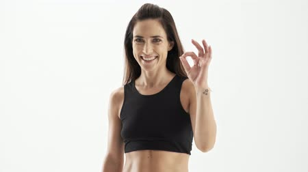 braçadeira : Happy attractive sporty brunette woman in black sportswear smiling and making okay gesture while looking at the camera over white background isolated Stock Footage