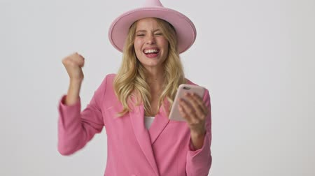çok güzel : Attractive young blonde woman in pink jacket and hat becoming very happy and making winner gesture with hand while using smartphone over gray background isolated Stok Video