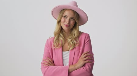 embarrassed : Cute young blonde woman in pink jacket and hat with crossed arms smiling while looking at the camera over gray background isolated