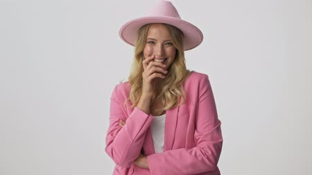 embarrassed : Cheerful young blonde woman in pink jacket and hat feeling embarrassed and closed her smile with hand while looking at the camera over gray background isolated