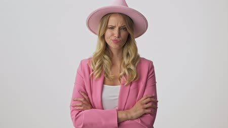 disapprove : Displeased young blonde woman in pink jacket and hat with crossed arms shaking her head negatively while looking at the camera over gray background isolated Stock Footage