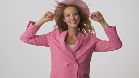 fryzura : Cheerful young blonde woman in pink jacket and hat touching her fluttering hair and dancing while looking at the camera over gray background isolated