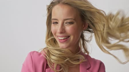 fryzura : Close up view of happy young blonde woman in pink jacket smiling and touching her fluttering hair while looking at the camera over gray background isolated Wideo