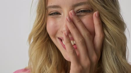 embarrassed : Cropped view of smiling young blonde woman feeling embarrassed and closed her face with hand while looking at the camera over gray background isolated Stock Footage