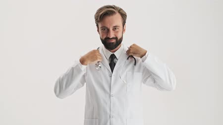 s rukama zkříženýma : Smiling young bearded man doctor in white professional coat putting stethoscope on his neck and crossed his arms while looking at the camera over gray background isolated