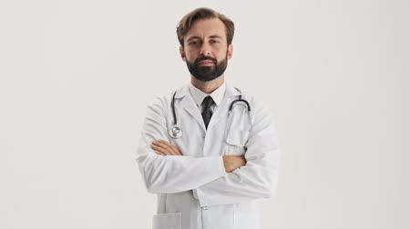 crossed : Attractive young bearded man doctor in white professional coat with stethoscope listening someone attentively and shaking his head positively while looking at the camera over gray background isolated