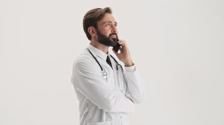 medics : Calm young bearded man doctor in white professional coat with stethoscope talking on smartphone over gray background isolated