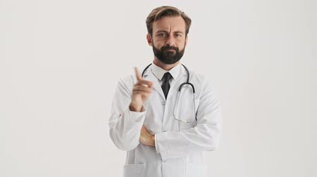 medics : Angry young bearded man doctor in white professional coat with stethoscope saying no with waving finger and shaking his head negatively while looking at the camera over gray background isolated Stock Footage