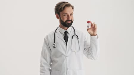 антибиотик : Handsome young bearded man doctor in white professional coat with stethoscope smiling and pointing with finger at the bottle with pills while looking at the camera over gray background isolated