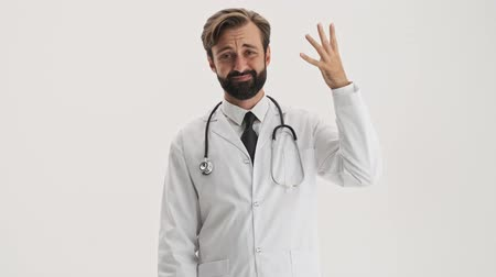 cápsula : Attractive young bearded man doctor in white professional coat with stethoscope throwing away a bottle with pills and showing no sign with waving finger while looking at the camera over gray background isolated