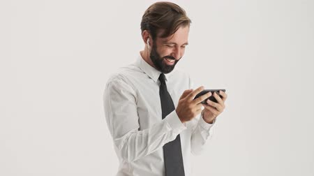 ing és nyakkendő : Cheerful young bearded business man with wireless earphones smiling and laughing while while watching video on smartphone over gray background isolated