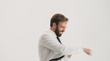 связать : Cheerful young bearded business man becoming very excited and making winner gesture with hands while looking at the camera over gray background isolated