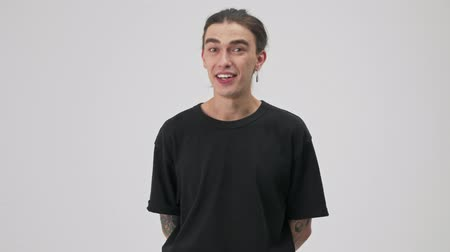 evet : Happy young tattooed brunette man in black t-shirt smiling and shaking his head approvingly while looking at the camera over gray background isolated