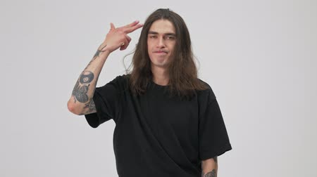 rockero : Upset young tattooed brunette man with long hair in black t-shirt feeling bored and making gun gesture with hand like shooting himself while looking at the camera over gray background isolated