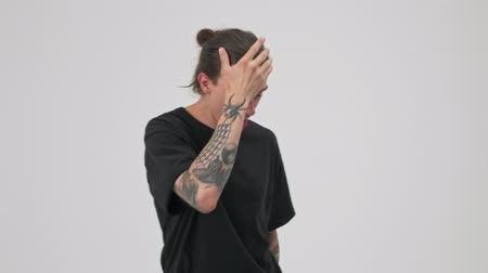 grimacing : Emotional young tattooed brunette man in black t-shirt becoming crazy and gesturing while looking at the camera over gray background isolated Stock Footage