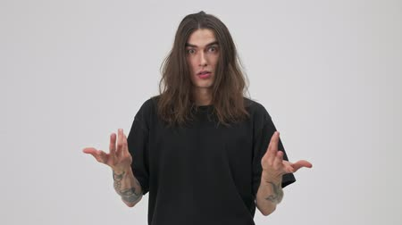 dispute : Displeased young tattooed brunette man with long hair in black t-shirt pointing at himself and asking who me while having a dispute with someone over gray background isolated