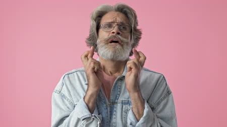 peça : Beautiful elderly stylish bearded man with gray hair in denim jacket crossing his fingers with hope and asking for something over pink background isolated