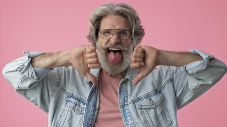grimacing : Displeased elderly stylish bearded man with gray hair in denim jacket making thumbs down gesture with hands and showing his tongue while looking at the camera over pink background isolated