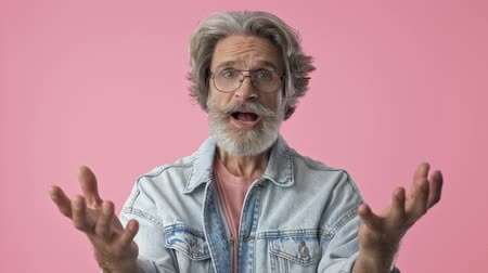 почему : Displeased elderly stylish bearded man with gray hair in denim jacket disagree with someone and gesturing with hands while looking at the camera over pink background isolated Стоковые видеозаписи