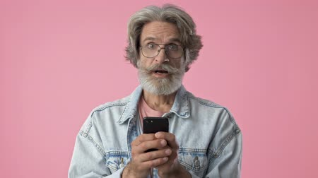 brim : Surprised elderly stylish bearded man with gray hair in denim jacket becoming happy and smiling while using smartphone over pink background isolated