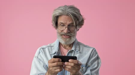 ötvenes : Excited elderly stylish bearded man with gray hair in denim jacket smiling and playing game on smartphone over pink background isolated