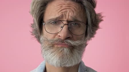 fifty : Close up view of upset elderly stylish bearded man with gray hair in denim jacket feeling sad over pink background isolated