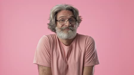 ombros : Confused elderly stylish bearded man with gray hair smiling and shrugging his shoulders while looking at the camera over pink background isolated