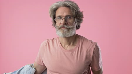 mustache : Confident elderly stylish bearded man with gray hair taking off his denim jacket while looking at the camera over pink background isolated Stock Footage