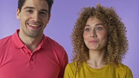 bater : Close up view of attractive young lovely couple knocking on the door and waiting but no one opening it over purple background isolated