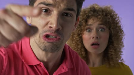 vecinos : Close up view of angry young couple arguing with their neighbors and gesturing over purple background isolated