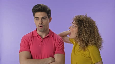 grimacing : Beautiful young aggressive woman yelling at her boyfriend. Handsome young man becoming annoyed and making stop gesture with hand to his girlfriend and going away. Attractive young couple arguing with each other over purple background isolated