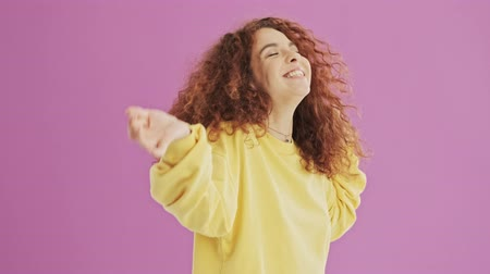 ruivo : Happy young redhead curly woman smiling and dancing over pink background isolated