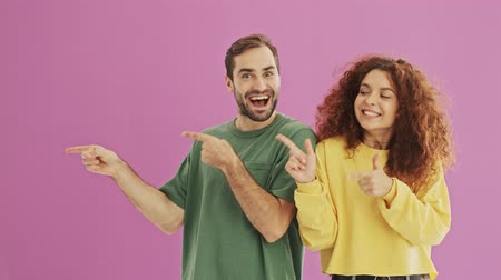 finom : Smiling positive young couple pointing to the side with fingers and making thumbs up gesture over pink background isolated