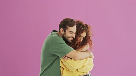 sorry : Smiling young bearded brunet man hugging his girlfriend. Cute young redhead curly woman feeling upset at her boyfriend. Beautiful young couple over pink background isolated Stock Footage