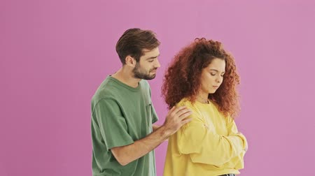 apologize : Handsome young bearded brunet man apologizing to his girlfriend. Cute young redhead curly woman feeling upset at her boyfriend. Beautiful young couple over pink background isolated