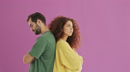 sorry : Upset young bearded brunet man turning around and hugging his girlfriend. Cute young redhead curly woman feeling upset at her boyfriend but forgiving and hugging him. Unhappy young couple staying back to back over pink background isolated