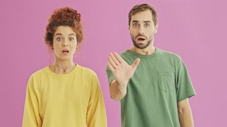 head over : Attractive serious young couple making stop gesture with hands and shaking their heads negatively over pink background isolated