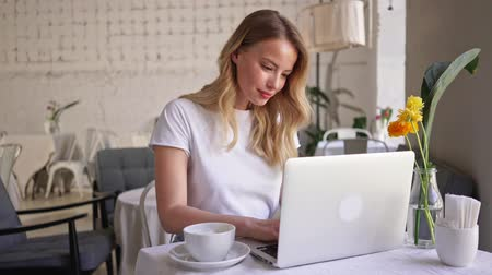 white shirt : Happy attractive young blonde woman drinking a cup of coffee and using laptop while sitting in cafe