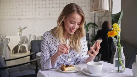 elegant dessert : Smiling beautiful young blonde woman eating cheesecake and looking at smartphone while sitting in cafe Stock Footage
