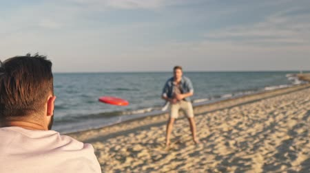 desfocado : Cropped back view of beautiful young cheerful man catching flying disk thrown by his friend while having fun at the seaside