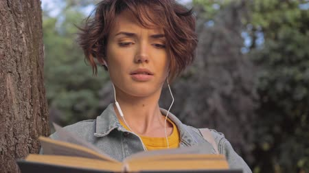 rövid : Attractive pleased young brunette woman in denim jacket listening music with earphones and reading book while leaning on a tree in the park