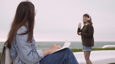desfocado : Concentrated cheerful young brunette girl in jeans and denim jacket writing in notebook and waving with hand to her friend while sitting at the pier near the sea