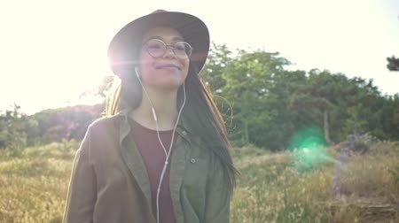 sluch : Beautiful smiling young brunette woman in brown hat listening music with earphones and looking around while walking in the park Dostupné videozáznamy
