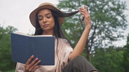 delici : Concentrated young brunette asian woman in hat playing with hair and chewing a straw while reading book in the park