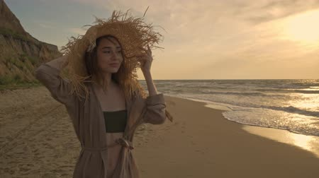 Çırpınan : Happy attractive young woman holding her straw hat and enjoying breeze while walking near the sea Stok Video