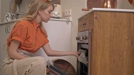 chemise à carreaux : Pleased cute young blonde woman with long curly hair opening electric oven and checking cake while cooking at the kitchen Vidéos Libres De Droits