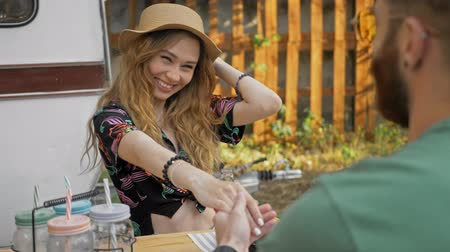 żart : Attractive happy young lovely couple holding hands together and laughing while sitting with friends near the trailer Wideo