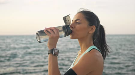 fitness tracker : Attractive smiling young sporty brunette woman in sportswear drinking water from the bottle after doing exercise outside near the sea