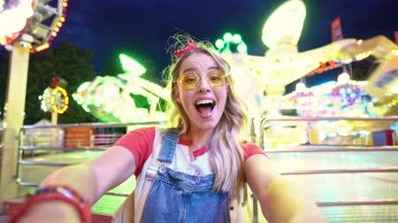 grimacing : Charming happy young blonde woman grimacing and having fun while taking selfie photo at amusement park